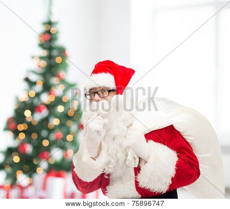 christmas, holidays and people concept - man in costume of santa claus with bag making hush gesture over living room and tree background