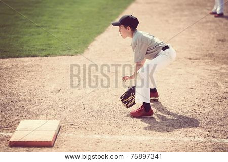 Boy ready at first base. Shallow focus