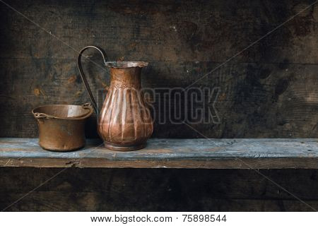 Copper jug and bowl on wood shelf