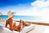 stock photo of mattress  - Beautiful young woman from back with white hat laying on white mattress and reading e-book with beautiful sea on background ** Note: Shallow depth of field - JPG