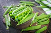 pic of snow peas  - green pea on the wooden board and on a table - JPG