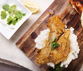 picture of lamb shanks  - Slow cooked lamb shanks served on wooden board with rice and gluten free naan bread - JPG