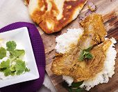 pic of lamb shanks  - Slow cooked lamb shanks served on wooden board with rice and gluten free naan bread