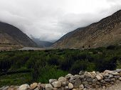 image of mustang  - Green fields of plants near a river in the dry Annapurna Himalayas of Mustang Nepal during monsoon - JPG