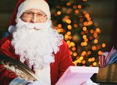 stock photo of letters to santa claus  - Portrait of Santa Claus reading and answering Christmas letters - JPG