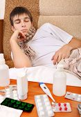 foto of home remedy  - Sad and Sick Teenager on the Sofa at the Home with Pills on foreground - JPG