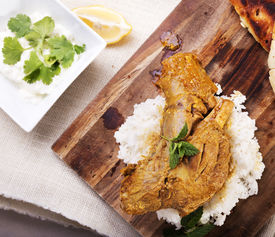 image of lamb shanks  - Slow cooked lamb shanks served on wooden board with rice and gluten free naan bread - JPG