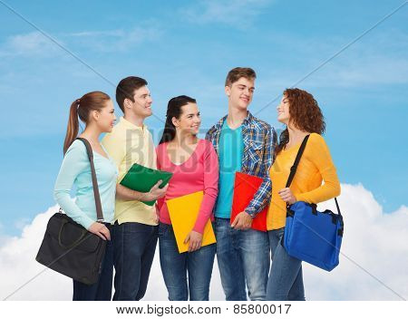 friendship, dream, education and people concept - group of smiling teenagers with folders and school bags over blue sky with white cloud background