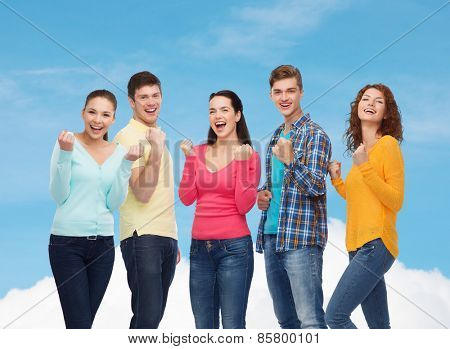 friendship, dream, teamwork, gesture and people concept - group of smiling teenagers showing triumph gesture over blue sky with white cloud background