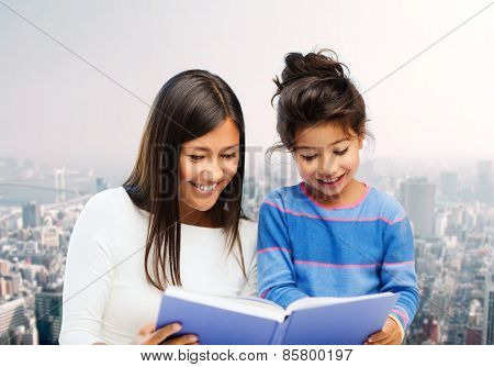 family, children, education and happy people concept - happy mother and little daughter reading book over city background