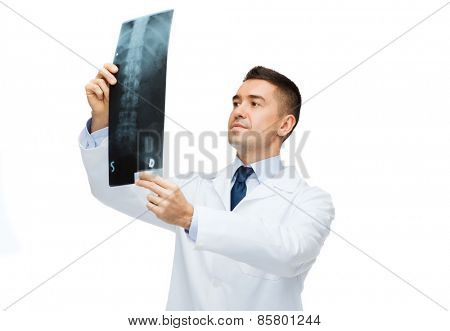 healthcare, rontgen, people and medicine concept - male doctor in white coat looking at x-ray