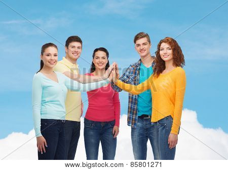 friendship, dream, teamwork, gesture and people concept - group of smiling teenagers making high five over blue sky with white cloud background
