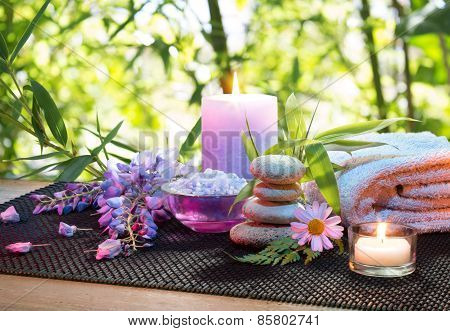 massage in the bamboo garden with violet flowers, candles