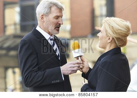 Female Journalist With Microphone Interviewing Businessman
