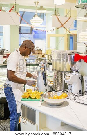 Black Man Extracting Orange Juice In Cafe