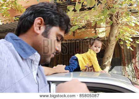 Indian father holding baby's feet while she is crawling on the car