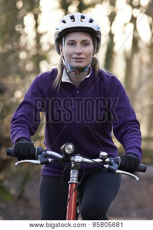 Woman Riding Mountain Bike Through Woodlands