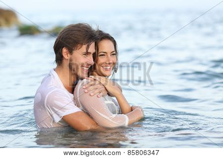 Happy Couple In Love Hugging And Bathing In The Beach