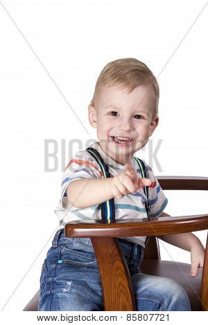 Boy pointing to the front on wooden chair