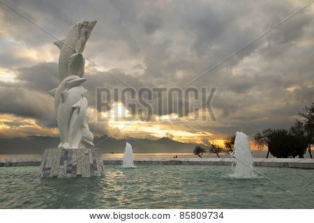 Famous Dolphin Statue In A Pond With A Cloudy Sky Background During Sunset In Karsiyaka, Izmir
