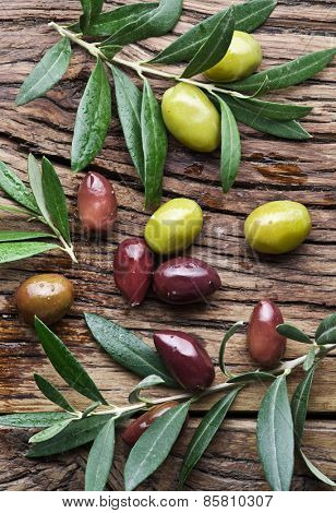 Olives and olive twigs on wooden table.