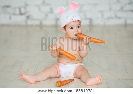 Portrait Of A Cute Baby Dressed In Easter Bunny Ears Sitting And Eating A Carrot