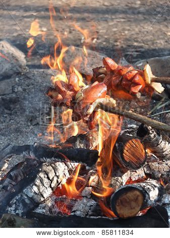 Roast Sausages Over A Fire In The Wild.