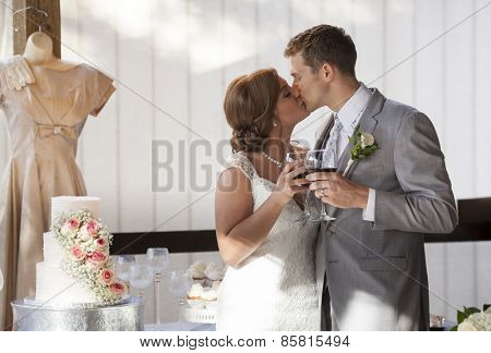 Bride and groom at cake cutting during reception doing wine toast with kiss