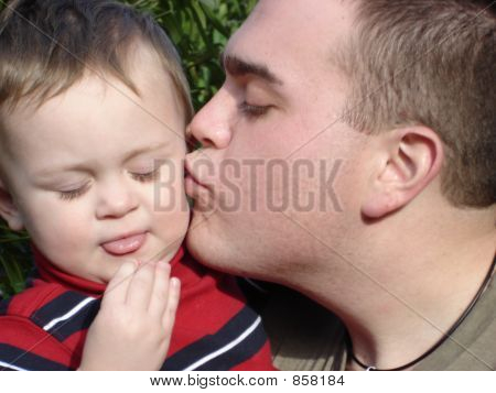 Father & Son. Father giving sone a kiss on the cheek. Toddler just ate sour candy