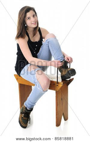 A beautiful teen girl looking at the viewer as she puts on her work boots.  On a white background.