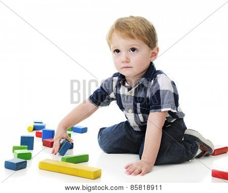 An adorable 2-year-old looking up as if to ask if it's okay for him to play with the colorful blocks surrounding him.  On a white background.