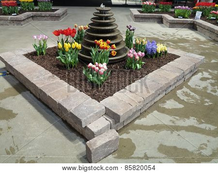 Colorful varieties of tulips and water fountain landscaping