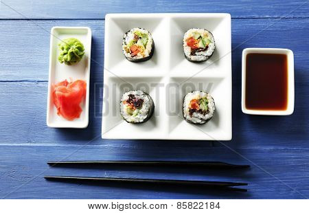 Vegetable sushi rolls on plate on color wooden background
