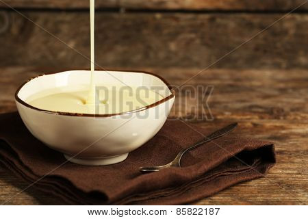 Bowl with condensed milk on napkin on wooden background