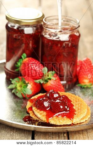 Jars of strawberry jam with berries and wafers on tray close up