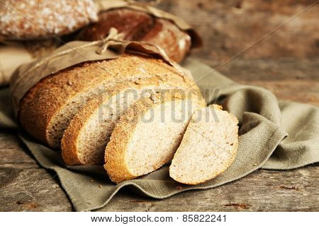 Sliced fresh bread, on old wooden table