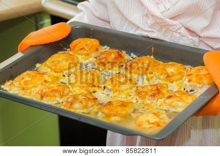 Woman holds meat baked in oven