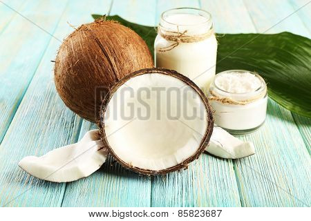 Fresh coconut oil in glassware and green leaf on color wooden table background