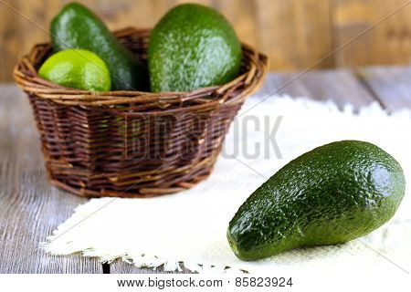 Avocado with limes in basket on wooden background