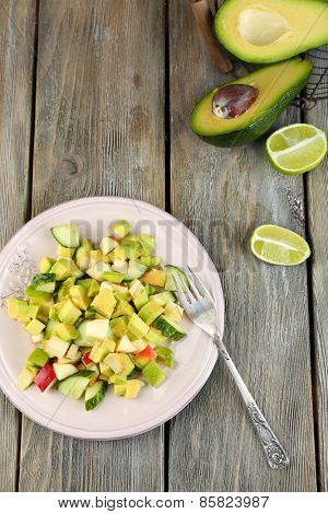 Salad with apple and avocado on plate with lime on wooden background