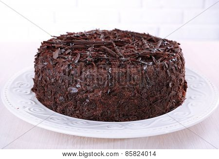 Tasty chocolate cake on table on brick wall background
