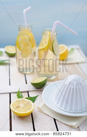 Fresh Lime And Lemon, Squeezer And Two Glasses Of Lemonade On Rustic Table