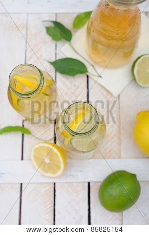 Jug And Glasses With Lemonade And Lemons And Lime On Rustic Table