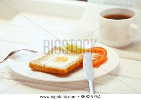 Scrambled egg with bread on plate with cup of tea on light background