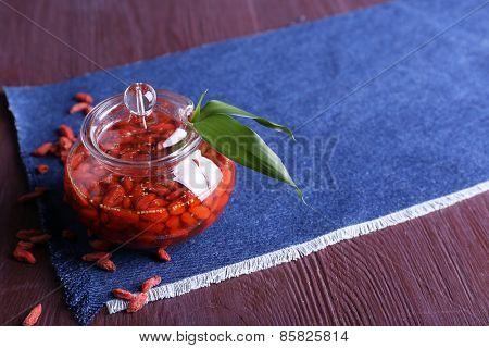 Jar of goji berry jam on napkin on wooden background
