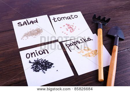 Different seeds on pieces of paper with gardening tools on wooden background