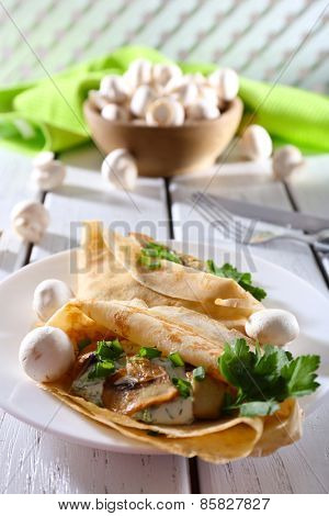 Pancakes with creamy mushrooms and greens in plate on wooden table, closeup