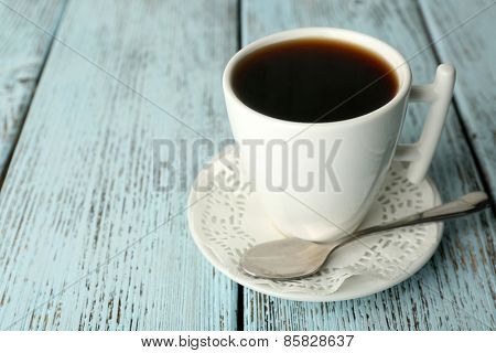 Cup of coffee with spoon on color rustic wooden background