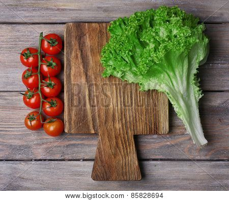 Cutting board with cherry tomatoes and lettuce on rustic wooden planks background