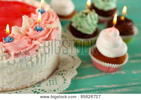 Delicious birthday cake with cupcakes on wooden background